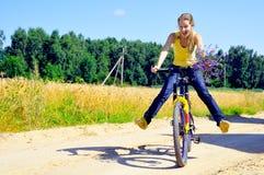 A menina de sorriso bonita monta a bicicleta no ro da vila Fotografia de Stock