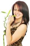 A menina de sorriso bonita morde uma folha de bambu Fotos de Stock Royalty Free