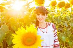 Menina de sorriso bonita no bordado em um campo do girassol Imagem de Stock Royalty Free
