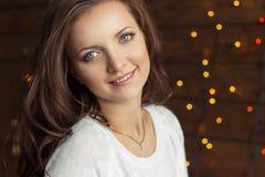 A menina de sorriso bonita no revestimento branco morno senta-se perto da janela ao lado da parede nas luzes Imagens de Stock