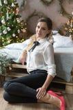 Menina de sorriso bonita no vestuário da noite perto da árvore do ano novo e com presentes Penteado e composição festivos Imagem de Stock