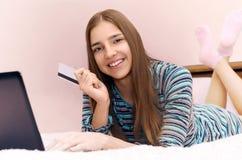 A menina de sorriso bonita nova faz a compra em linha usando o portátil Fotos de Stock