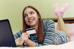 A menina de sorriso bonita nova faz a compra em linha usando o portátil Fotos de Stock Royalty Free