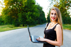 Menina de sorriso bonita nova que guarda o portátil na estrada Imagem de Stock