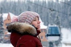 Menina de sorriso bonita nova que olha lateralmente no chapéu feito malha cor-de-rosa com pompon e nos mitenes brancos com teste  imagens de stock royalty free