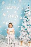 Menina de sorriso bonita pequena com um presente em suas mãos Imagens de Stock Royalty Free