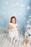 Menina de sorriso bonita pequena com um presente em suas mãos Fotos de Stock Royalty Free