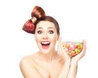 Menina de sorriso bonita que come doces de uma bacia fotos de stock
