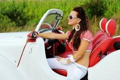 Menina de sorriso bonita que conduz um carro retro branco fotos de stock