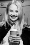 Menina de sorriso bonita que guarda a xícara de café de papel, foto preto-branca foto de stock