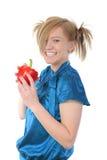 Menina de sorriso bonita que prende uma pimenta vermelha. Imagem de Stock Royalty Free