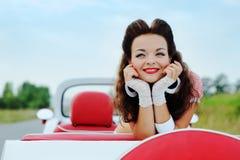 Menina de sorriso bonita que senta-se no carro do vintage foto de stock