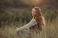 A menina de sorriso bonito com sorriso maravilhoso, bonito, branco e os bordos vermelhos olha o por do sol, senta-se em montes, n Fotografia de Stock