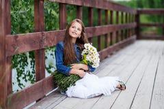 Menina de sorriso bonito com um ramalhete das margaridas no cais que sonham com os pés descalços Fotografia de Stock