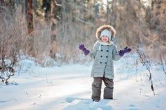 Menina de sorriso bonito da criança que está na neve na floresta ensolarada do inverno Fotografia de Stock Royalty Free