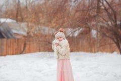 Menina de sorriso bonito da criança que guarda o coelho que anda na neve no parque olhando a câmera Infância Chapéu, camiseta e s Imagens de Stock