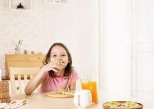 Menina de sorriso bonito do preteen que come o café da manhã saudável: sanduíche e suco de laranja do abacate Conceito saudável d foto de stock royalty free