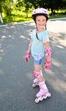 Menina de sorriso bonito em patins de rolo cor-de-rosa foto de stock