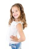 Menina de sorriso bonito nas calças de brim isoladas fotografia de stock