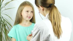 Menina de sorriso bonito no hospital Doutor com a moça de exame do estetoscópio vídeos de arquivo