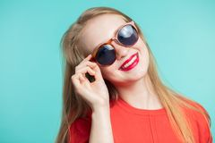 Menina de sorriso bonito nova nos óculos de sol foto de stock