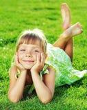 Menina de sorriso bonito que encontra-se em uma grama verde no parque na Imagens de Stock Royalty Free