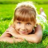 Menina de sorriso bonito que encontra-se em uma grama verde no parque na Foto de Stock Royalty Free