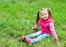 Menina de sorriso bonito que encontra-se na grama no prado foto de stock royalty free