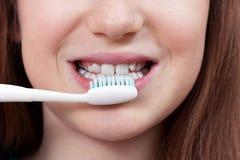 Menina de sorriso bonito que escova seus dentes fotos de stock royalty free