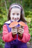 Menina de sorriso bonito que prende um cogumelo Foto de Stock Royalty Free