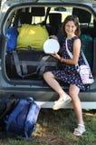 A menina de sorriso carrega sua bolsa no carro antes de sair para imagens de stock royalty free