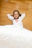 Menina de sorriso coberta com a cobertura que encontra-se no assoalho de madeira Foto de Stock Royalty Free