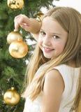 Menina de sorriso com as esferas do Natal ao lado do tr verde Imagem de Stock