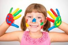 Menina de sorriso com as mãos pintadas em pinturas coloridas Fotos de Stock Royalty Free