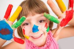 Menina de sorriso com as mãos pintadas em pinturas coloridas Foto de Stock