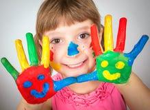 Menina de sorriso com as mãos pintadas em pinturas coloridas Fotos de Stock