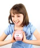 Menina de sorriso com banco piggy Imagens de Stock