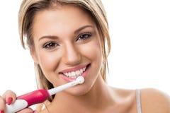 Menina de sorriso com escova de dentes elétrica imagem de stock royalty free