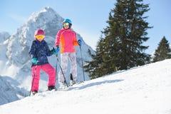 Menina de sorriso com esqui da mãe em montanhas dos cumes Fotografia de Stock