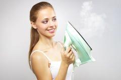 Menina de sorriso com ferro. no cinza Fotos de Stock Royalty Free