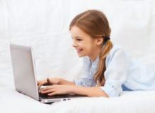 Menina de sorriso com laptop em casa Fotos de Stock