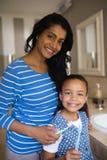 Menina de sorriso com a mãe que guarda escovas de dentes no banheiro fotos de stock