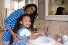 Menina de sorriso com mãos de lavagem da mãe no dissipador do banheiro fotografia de stock royalty free