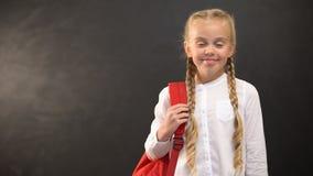 Menina de sorriso com mochila que sorri na câmera no fundo do quadro-negro, educação vídeos de arquivo