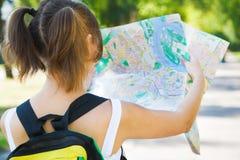 Menina de sorriso com o mapa da cidade da terra arrendada da trouxa Imagem de Stock