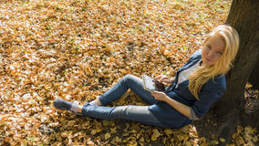 Menina de sorriso com o PC da tabuleta no outono Imagem de Stock