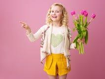 Menina de sorriso com o ramalhete das tulipas que apontam em algo Foto de Stock