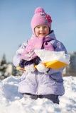 A menina de sorriso com pá mostra a neve no monte de neve Fotografia de Stock Royalty Free