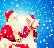 Menina de sorriso com Papai Noel e presentes Foto de Stock Royalty Free
