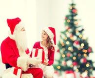 Menina de sorriso com Papai Noel e presentes Fotografia de Stock Royalty Free